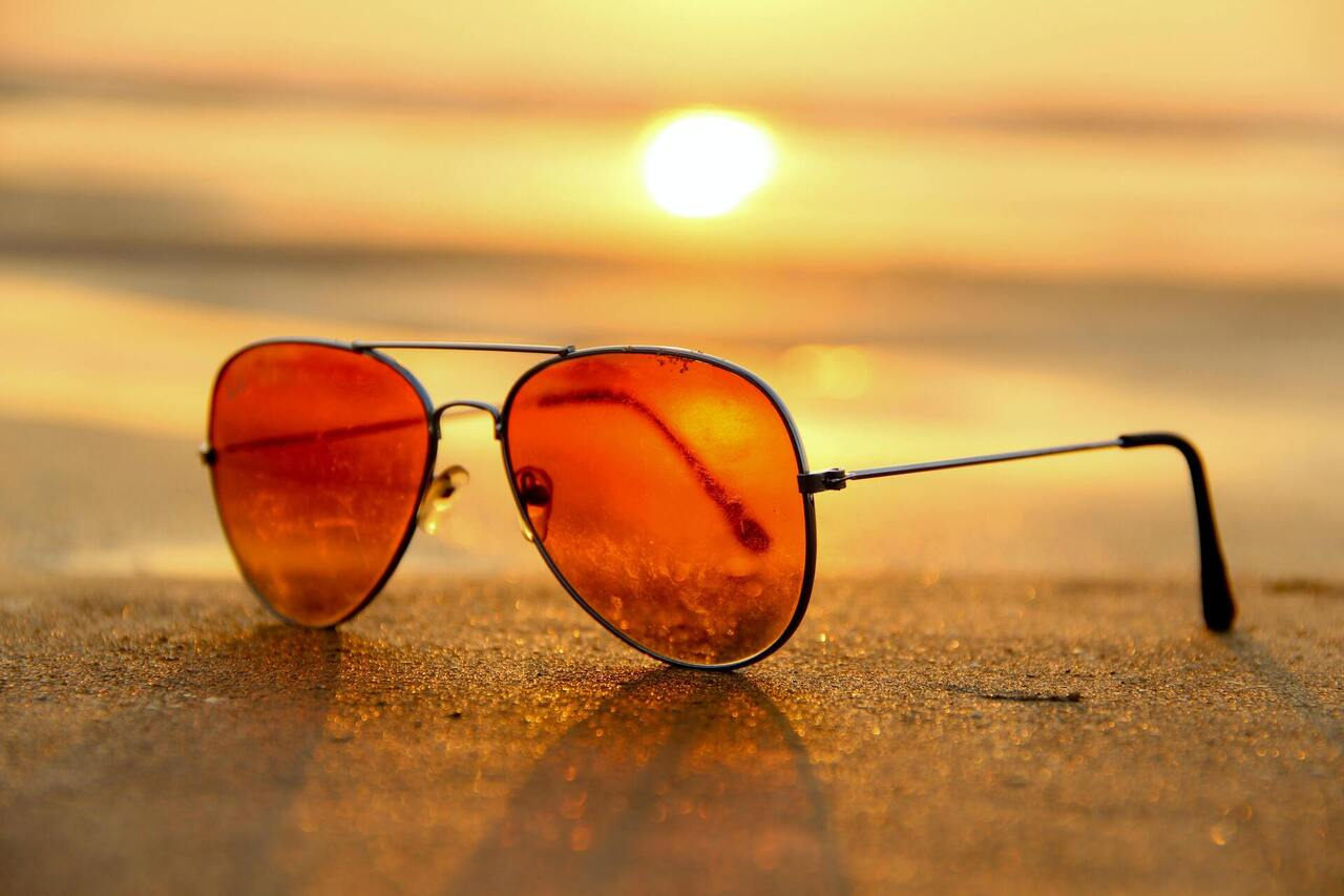 Red Lens Sunglasses on Sand Near Sea at Sunset Selective Focus Photography