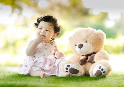 Baby Sitting on Green Grass Beside Bear Plush Toy 5K