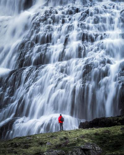 Man Standing in Front of Big Waterfall