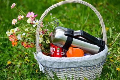 Picnic Basket With Flower Bouquet on Grass Meadow