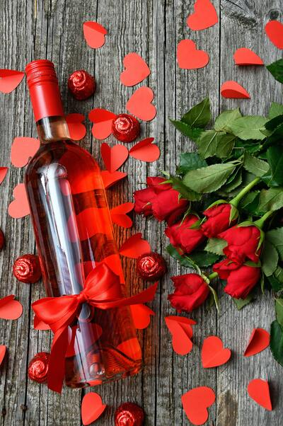Rose Wine With Red Roses on Wood