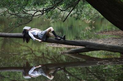 School Girl Sleeping on Tree Over Lake